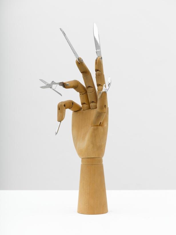 "Damián Ortega, The Part played by Labour in the Transition from Ape to Man. ""Darin Anteil der Arbeit an der Menschwerdung des Affen"" (F. Engel) 2013. Wooden hand model and steel knives 10 1/4 x 4 5/16 x 2 3/4 in. (26 x 11 x 7 cm) © Damián Ortega. Photo: Ben Westoby. Courtesy White Cube."