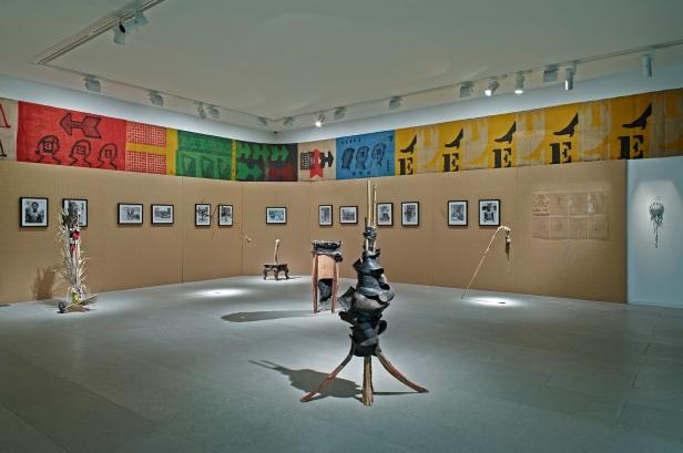 'Lições da Escuridão, Sala 2. Interface Makonde, Otelo Fabião (esculturas), 2012; Fotografias de Manuel Viegas Guerreiro; faixa em juta de José de Guimarães. Cortesia Centro Internacional das Artes José de Guimarães, 2013
