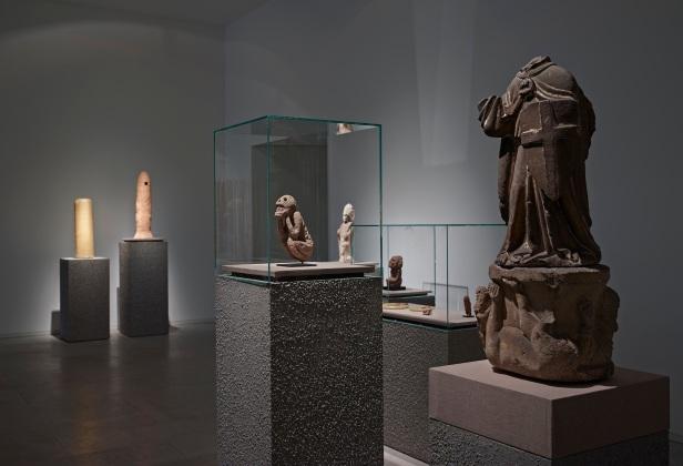 'Lições da Escuridão, Sala 8. Vista de pormenor. Em primeiro plano: São Miguel Arcanjo (século XV); Macaco, Atzeca (1200-1518 d.c.). Cortesia Centro Internacional das Artes José de Guimarães, 2013