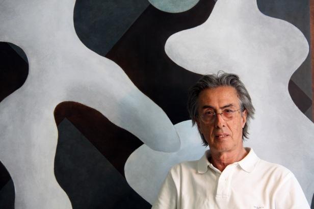 O artista Justino Alves fotografado junto a uma da suas telas. Cortesia do artista e de Bloco 103 -Arte Contemporânea.
