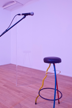 "André Romão, Ghost sitting on a bar stool, 2015 ""Duplex"" chair by Javier Mariscal and Fernando Salas, 1980. Microphone, stand, speaker, text, ghost. Sculpture I, 2015 Acrylic glass. Sculpture II, 2015 Acrylic glass. Photo by Roberto Ruiz Arguedas. Courtesy of the artist and The Green Parrot."